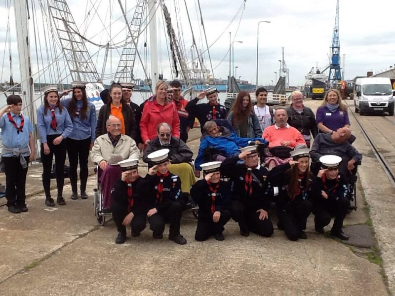 Kids wearing sailor costumes with disabled guests and carers on the docks