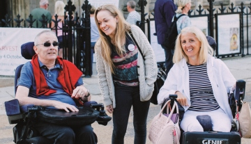 Revitalise guests in wheelchair with volunteer on accessible excursion
