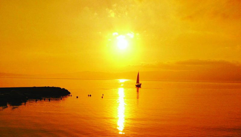 Beautiful golden sunset with boat in distance